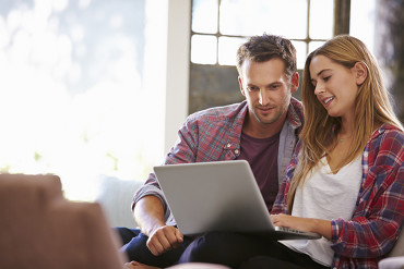 couple sitting on couch together looking at computer